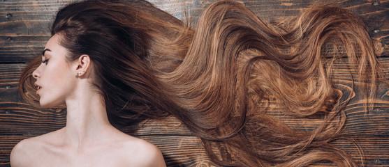 Woman with beautiful long hair on wooden background. Long hair. Trendy haircuts. Beauty hair Salon. © tverdohlib