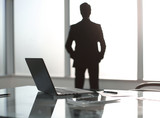 businessman stands in a modern office and looks out the window.