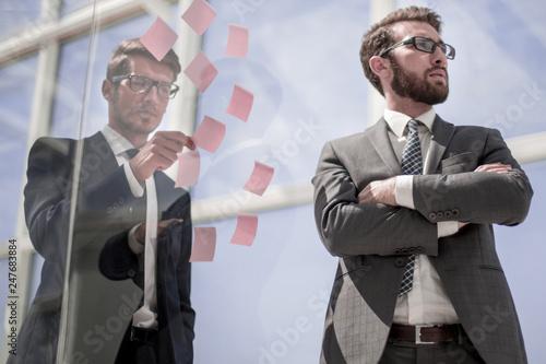 Fototapeta employees standing near a transparent office wall