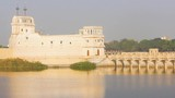 Beautiful Palace structure in middle of the Lakhota lake Jamnagar city stock video I Palace in lake with golden shine - 247684084
