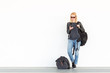 Fashionable young woman using her mobile phone while standing and waiting against plain white wall on the station whit travel bag by her side. Copy space on white wall.