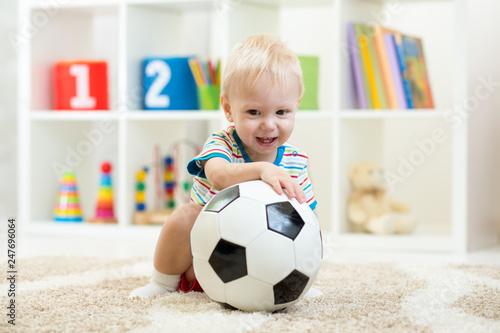Leinwandbild Motiv Nursery child boy playing with soccer-ball at home or daycare