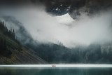 A boat in the misty Lake Louise in Banff National Park, Canada