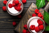 Raspberry smoothie in glass jars with fresh berry and yogurt on vintage wooden kitchen table background, flat lay, top view