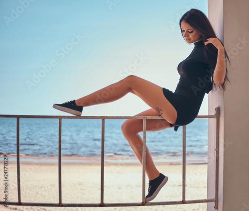 Leinwanddruck Bild Young beautiful girl with a tattoo on her leg sitting on the railing against the beautiful sea coast