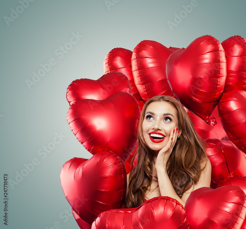 Leinwandbild Motiv Young woman with balloons red heart. Surprised girl with red lips makeup, curly hair and cute smile looking up. Surprise, sale and Valentine's day concept . Expressive facial expressions