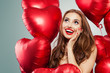 Excited young woman holding balloons red heart. Surprised girl with red lips makeup, long curly hair and cute smile