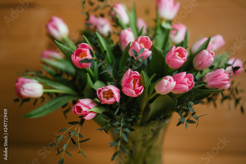Leinwanddruck Bild A bouquet of pink tulips in a beautiful crystal vase on wooden background. Spring