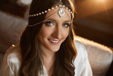 Portrait of beautiful and fashionable brunette model girl with blue eyes, with trendy jewelry on her head and with professional bright makeup
