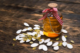 Pumpkin seed oil in the bottle on the wooden table background. - 247746806