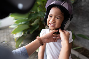 beautiful mother help her child to put on a helmet. safety first before riding a motorbike