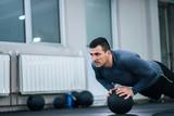 Muscular man doing push-ups on a ball.