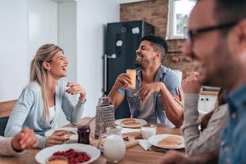 Group of happy people having breakfast together, eating pancakes.