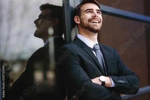 Leinwandbild Motiv Cheerful businessman standing outside office building
