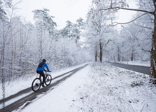 man on mountain bike follows trail in snow during winter in the netherlands near utrecht and austerlitz