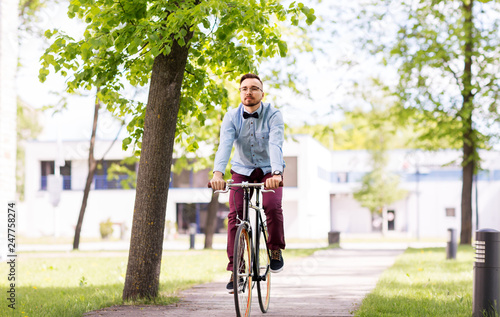 people, style and lifestyle - happy young hipster man riding fixed gear bike on city street