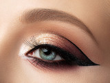 Close up of beautiful woman eye with multicolored fashion makeup and modern eyeliner wing. Studio shot - 247761010