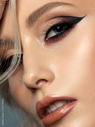 Leinwandbild Motiv Portrait of young beautiful woman with evening make up. Modern fashion eyeliner wing. Studio shot. Extreme closeup, partial face view