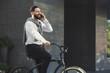 Leinwandbild Motiv Businessman stop bicycle to talk on phone