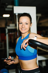 Young cheerful fitness woman working out in the gym. Fit girl taking a break for texting on smartphone.