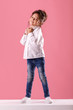 Leinwanddruck Bild - Full length portrait of adorable smiling little girl in white shirt with hairstyle looking to camera on pink background.