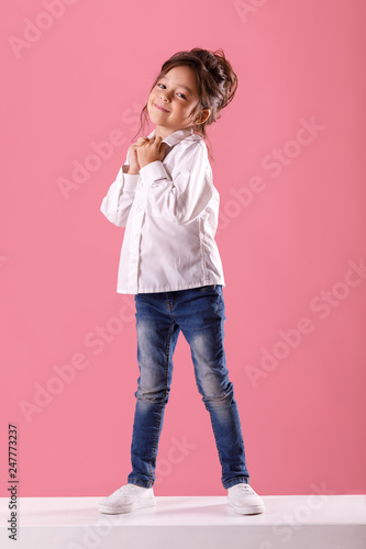 Leinwanddruck Bild Full length portrait of adorable smiling little girl in white shirt with hairstyle looking to camera on pink background.
