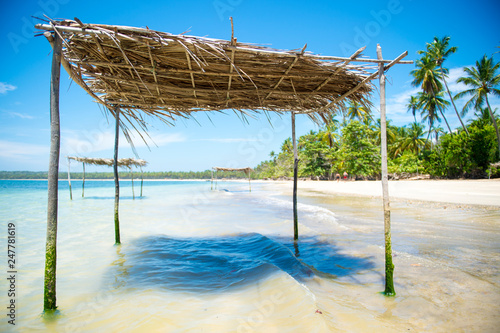 Rustic palm frond and tree branch palapa umbrella waiting to shade visitors to the shallow waters on a remote palm fringed tropical beach in Bahia, Brazil