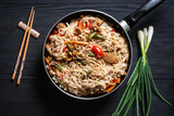 .Thai noodle wok with chopsticks in a frying pan on a black wooden background with a place for copy space - 247783091