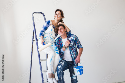 Leinwandbild Motiv Redecoration, family and renovation concept - Funny young woman and man standing on the ladder