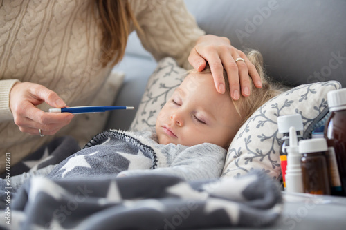Leinwanddruck Bild Sick child, toddler boy lying in bed with a fever, resting at home