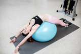 Young woman stretching on a fitness ball during the spine treatment at the rehabilitation gym