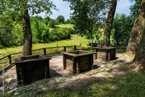 Three ancient wooden wells at the edge of the forest - 247802606
