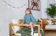 Portrait of little girl in blue sweater, sitting at armchair, looking at camera, smiling.