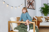 Portrait of little girl in blue sweater, sitting at armchair, looking at camera, smiling. - 247811609