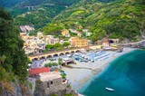 Top aerial view of green hill, railway, beach and harbor of Monterosso town village at sunset dusk, Genoa Gulf, Ligurian Sea, National park Cinque Terre, La Spezia, Liguria, Italy - 247813066