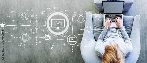 Leinwandbild Motiv E-Learning with man using a laptop in a modern gray chair
