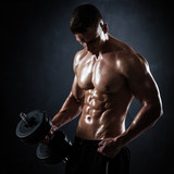 Athletic shirtless young male fitness model with dumbbells