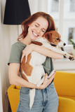 Loving young redhead woman hugging her dog