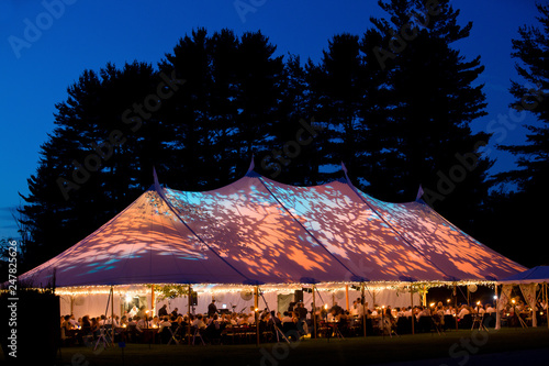 Zobacz obraz Wedding tent at night - Special event tent lit up from the inside with dark blue night time sky and trees