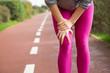 Leinwanddruck Bild - Female jogger wearing pink tights, injuring knee