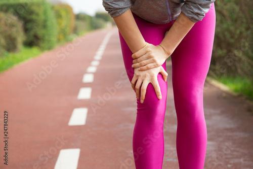 Leinwanddruck Bild Female jogger wearing pink tights, injuring knee