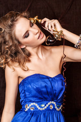 Portrait of a charming woman with stylish curly hairstyle wearing a blue dress talking on vintage old phone in retro style © Fxquadro