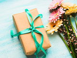 Beautiful flowers and gift box on pastel green