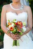 bride holding her wedding bouquet of flowers with green, red, white, and orange flowers