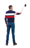 back view of standing young guy with smartphone in the hands of.