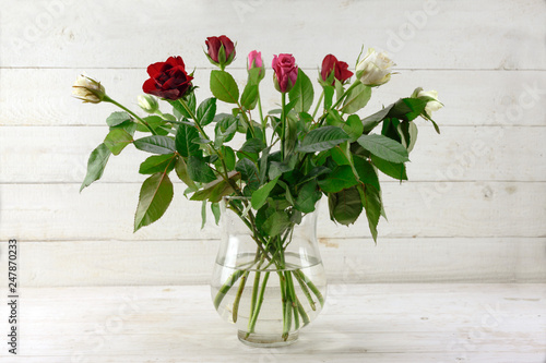 bouquet with roses in red, pink and white in a glass vase on light grey painted rustic wood, copy space