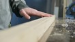 Close-up of a male carpenter's hand checking the smoothness and suitability of a wooden plank after processing