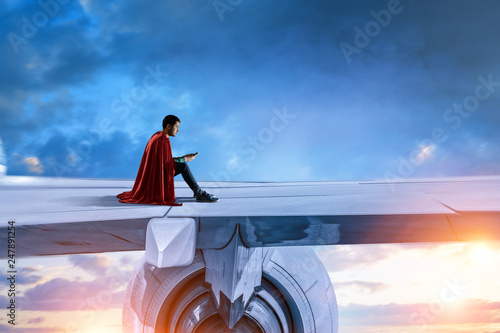 Young businessman super hero on edge of airplane wing