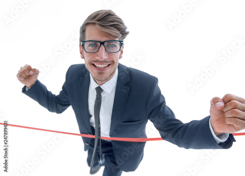 Cheerful businessman crossing red finish line