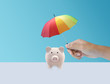 Leinwandbild Motiv pink piggy ceramic bank with colorful rainbow umbrella, safe insurance